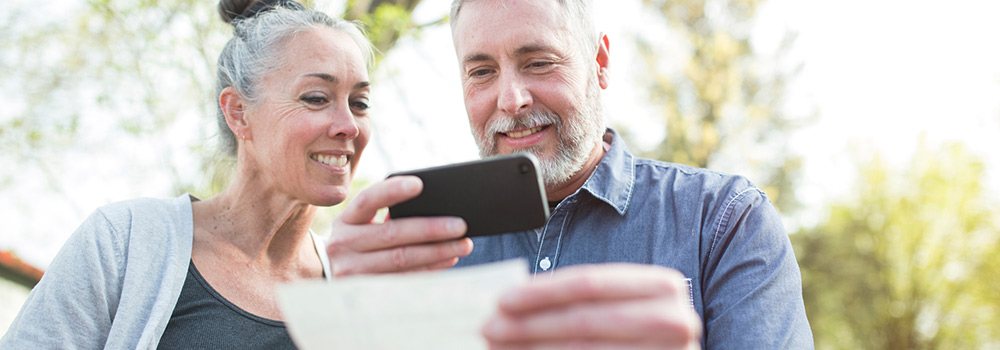 older couple using mobile phone for check deposit